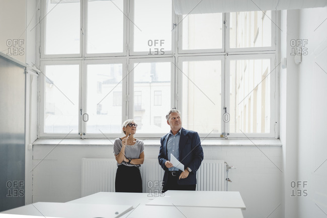 Businessman and businesswoman discussing in new office