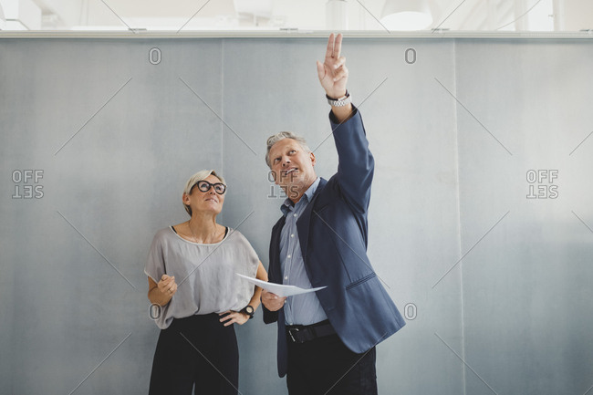 Mature businessman holding documents while discussing with businesswoman against wall in new office