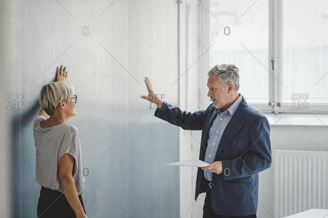 Mature businessman holding documents while discussing with female colleague in new office