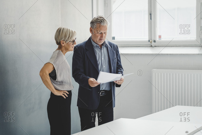 Mature businessman reading documents while discussing with female colleague in new office