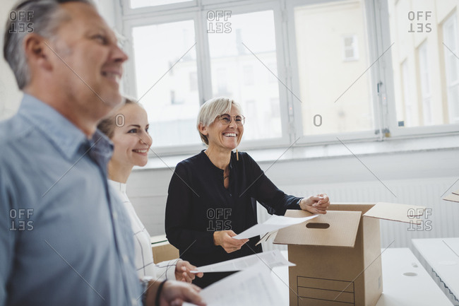 Smiling mature businessman with colleague unpacking cardboard box in new office