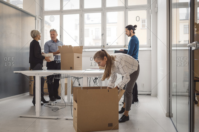 Multi-ethnic businessmen and businesswomen unpacking in new office