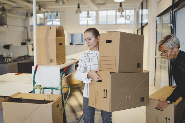 Businesswomen moving cardboard boxes into new office