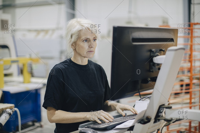 Serious mature woman using computer while standing in industry