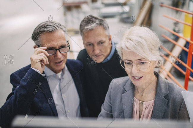 High angle view of businesswoman with colleagues in meeting at industry