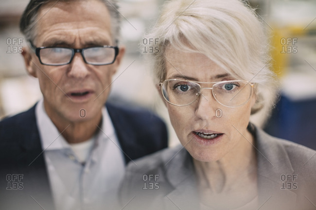 Close-up of serious business people wearing eyeglasses at industry