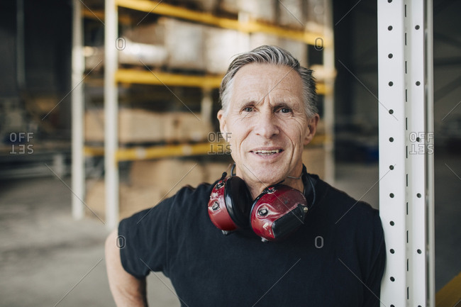 Portrait of smiling senior worker leaning on rack at industry