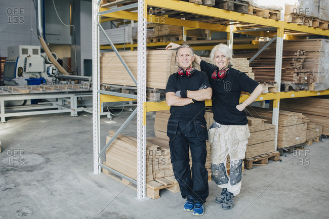 Full length portrait of smiling workers standing by rack in industry