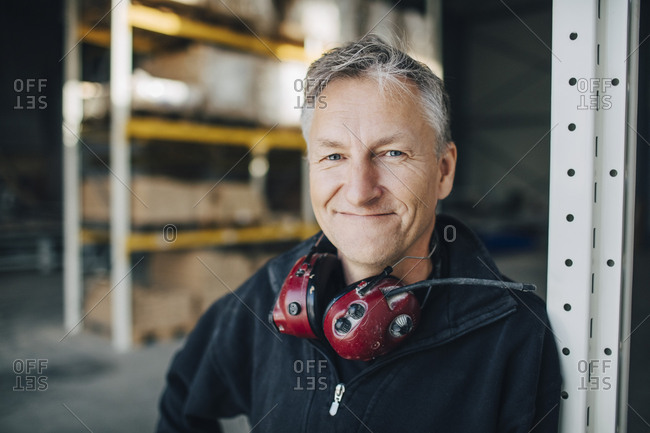 Close-up portrait of mature worker with ear protectors leaning on rack at industry