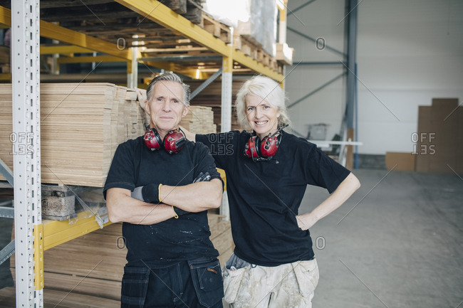 Portrait of smiling male and female workers standing by rack in industry