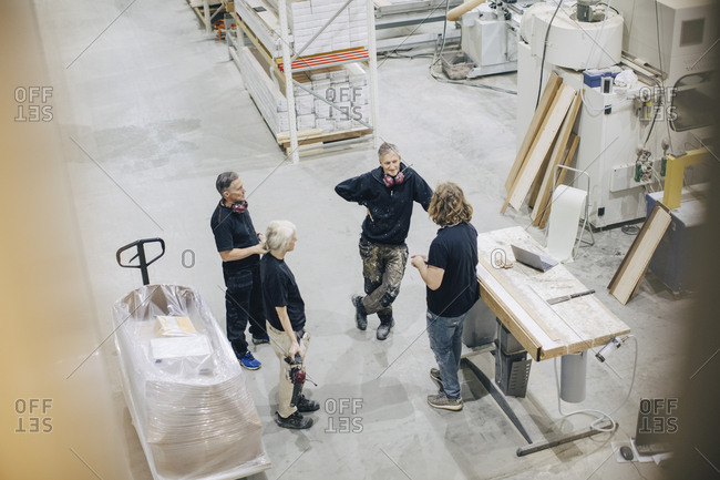 High angle view of workers discussing in meeting at industry