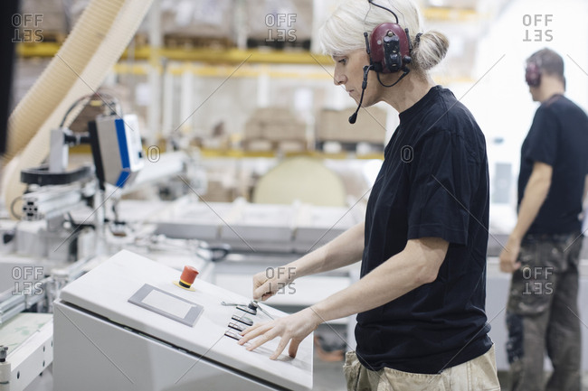 Side view of female worker wearing ear protectors operating machine at industry