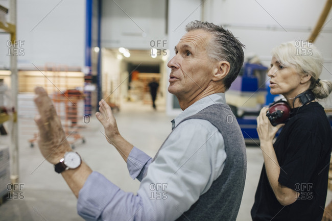 Entrepreneur discussing with female colleague while working at industry