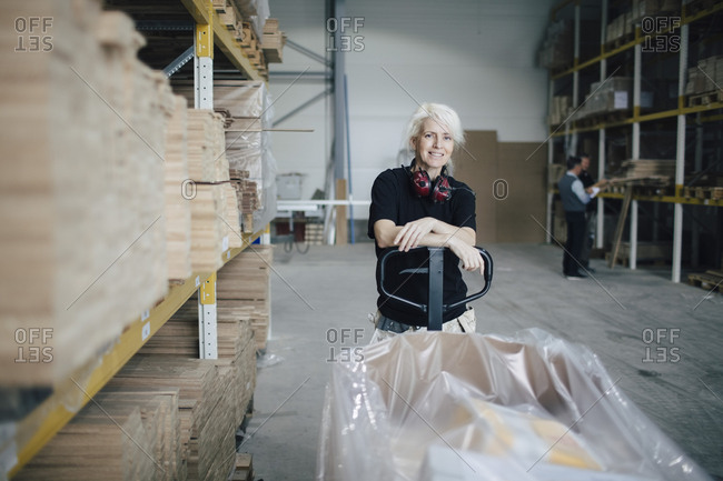 Portrait of smiling worker leaning on pallet jack by wooden planks at industry