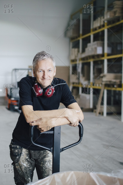 Portrait of mature worker leaning on pallet jack by stack at industry