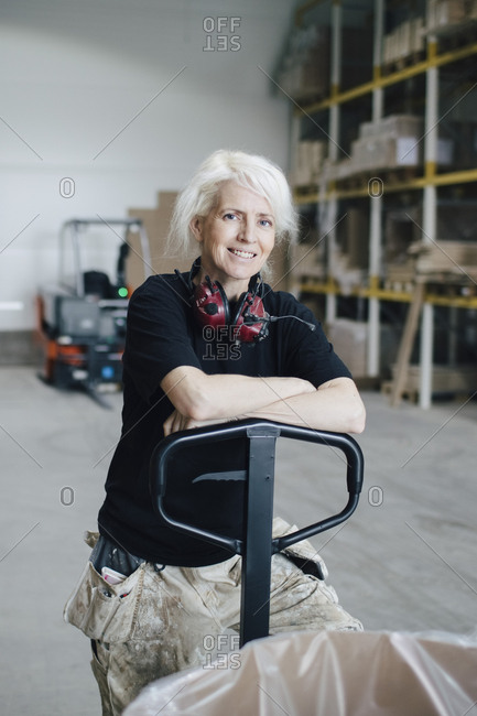 Portrait of smiling mature woman leaning on pallet jack at industry