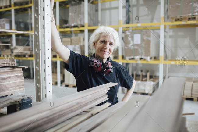 Portrait of smiling woman standing by wooden planks on rack in industry