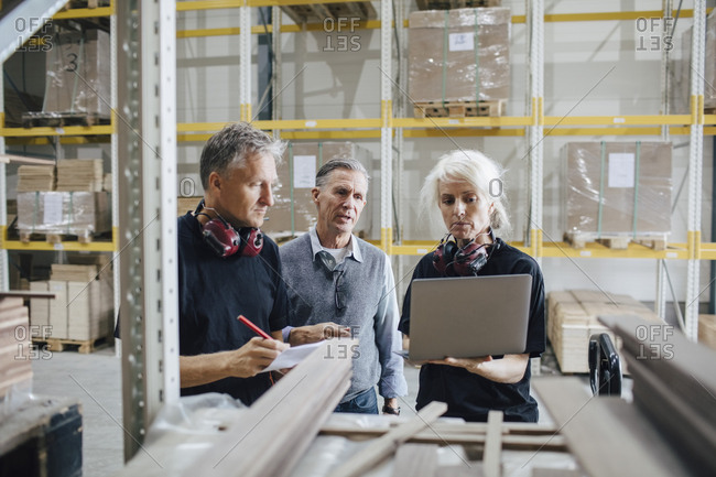 Female worker showing laptop to colleagues while standing by rack in industry