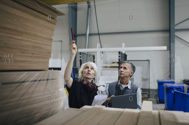 Mature woman discussing with colleague while examining wooden planks at industry