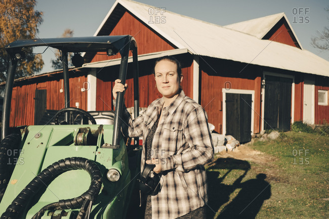 Portrait of confident female farmer standing by agricultural vehicle against barn