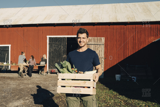 Portrait of smiling mid adult man carrying crate full of organic vegetables with barn in background