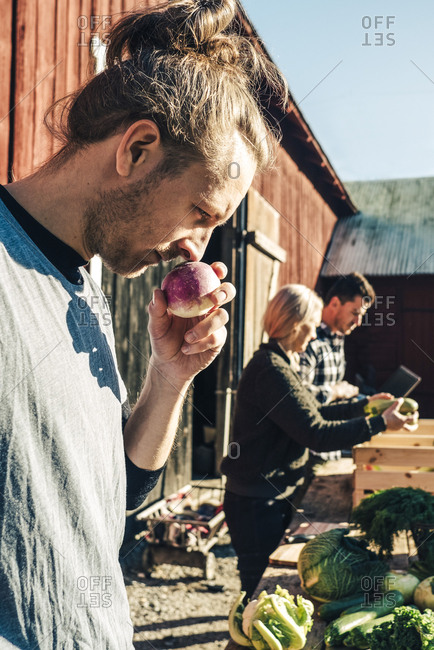 Mid adult male farmer smelling turnip with friends in background at market