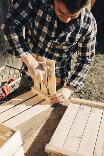 Mid adult male farmer making wooden crate using screwdriver
