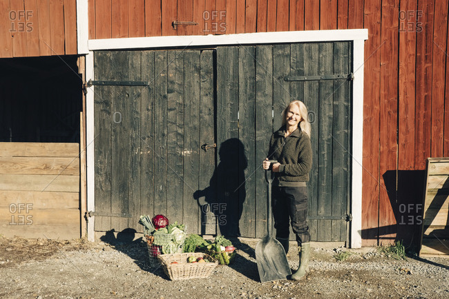 Full length portrait of female farmer with shovel standing by organic vegetables outside barn