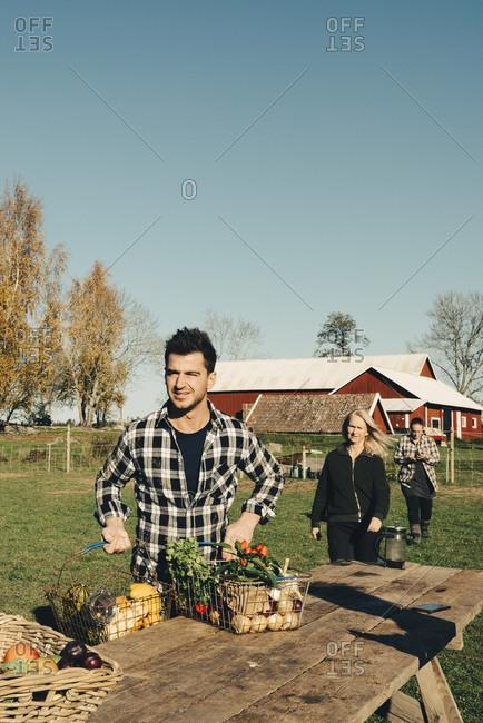 Mid adult man selling organic vegetables on table at farmer's market