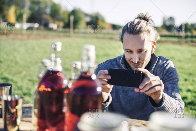 Mid adult man photographing bottles displayed for sale at farmer's market