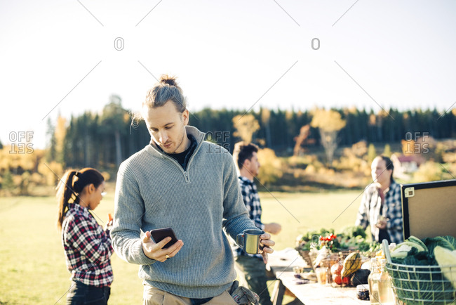 Mid adult male farmer using mobile phone while holding coffee cup with friends in background