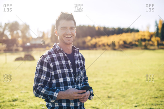 Portrait of smiling mid adult male farmer holding mobile phone while standing on field