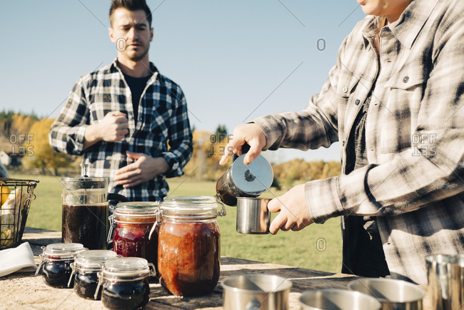 Mid adult male farmer looking at woman pouring coffee into cup at farmer's market