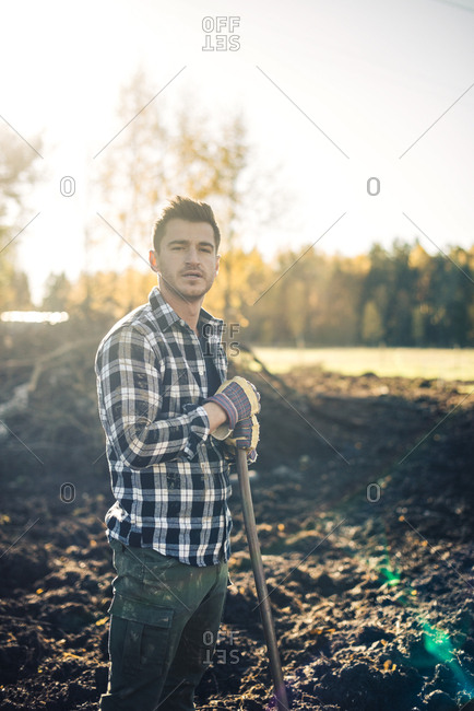 Portrait of confident male farmer with shovel standing on organic farm