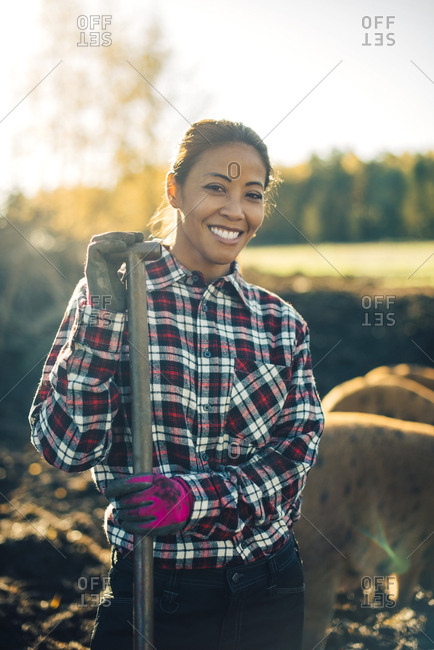 Portrait of smiling mid adult female farmer holding shovel with pigs in background at organic farm