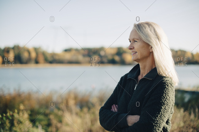 Thoughtful female farmer standing arms crossed at organic farm