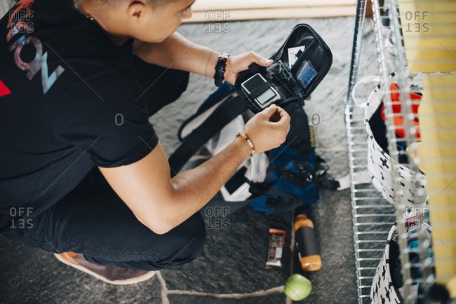 High angle view of man preparing diabetes kit while crouching at home