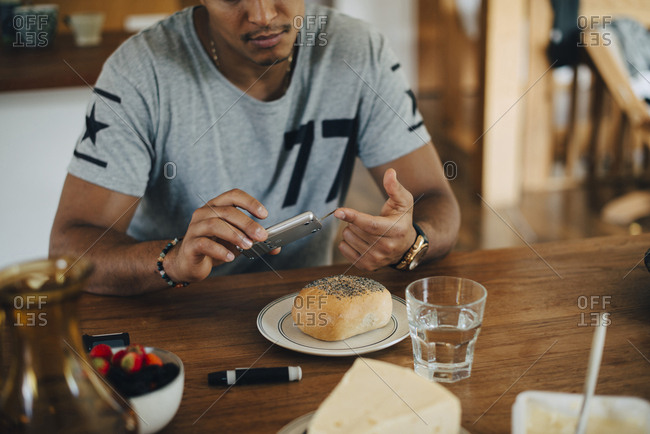 Man doing diabetes test while having breakfast at table