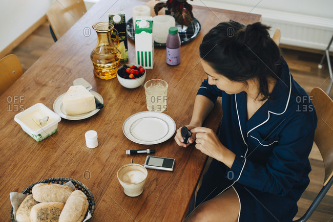 Woman checking diabetes while having breakfast on table at home