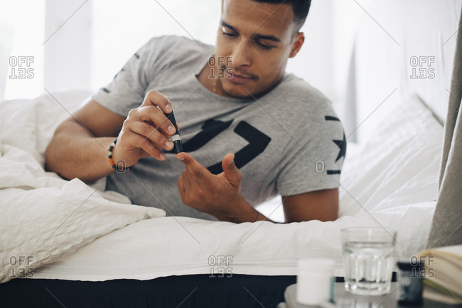 Man doing medical test while lying on bed at home
