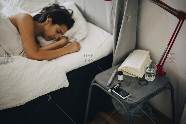 Woman lying on bed by diabetes kit ion bedroom