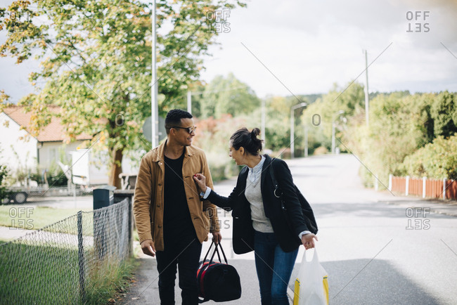 Smiling man and woman talking while walking on street in city during sunny day