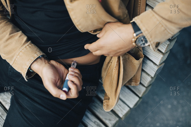 Midsection of man injecting insulin while sitting on bench