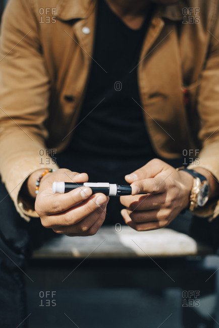 Midsection of man checking blood sugar level while sitting on bench