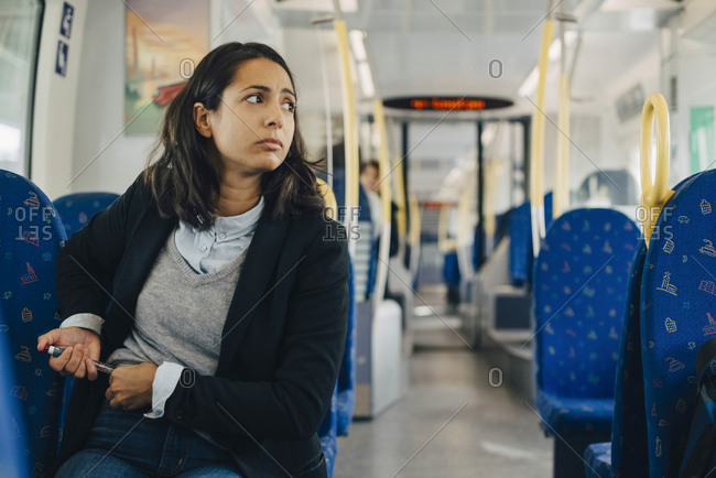 Woman using injection pen while sitting in train