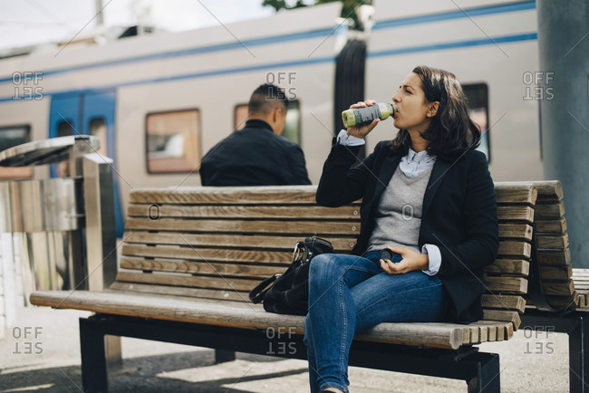 Woman drinking juice while sitting on bench at platform by train