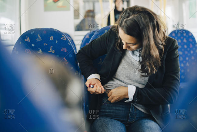 Woman injecting in abdomen while sitting by window in train