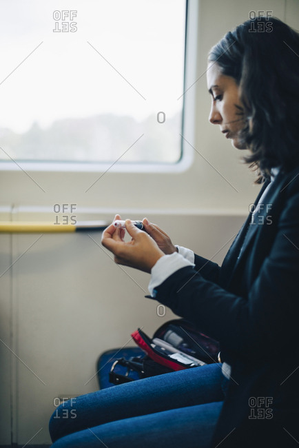 Woman looking at injection pen while sitting by window in train