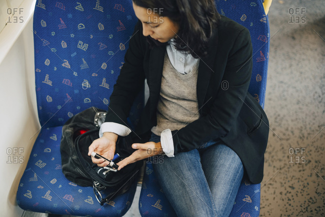 Woman doing blood test while traveling in train