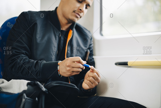 Man doing blood test while sitting in train